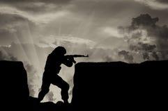Terrorist med ett vapen i diken mot himmel i rök Arkivbilder