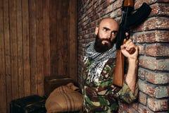 Terrorist med geväret som döljer bak en vägg arkivbild