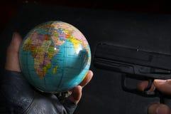 Terrorist put a gun to globe. Royalty Free Stock Photography