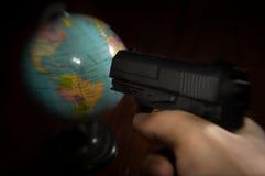 Terrorist put a gun to globe. Stock Photo