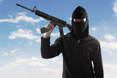 Terrorist with rifle and mask under blue sky Royalty Free Stock Images