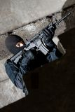 Terrorist with a rifle targeting. Armed and dangerous man in black uniform aiming the target Royalty Free Stock Photography