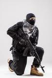 Terrorist som rymmer en maskingevär i hans händer som isoleras över vit Arkivbilder