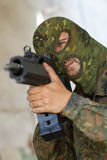 Terrorist targeting with a gun. Man in camouflage mask aiming the target with automatic G36 rifle Royalty Free Stock Images