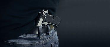 Terrorist thief man holding gun in his hand. Hidden gun. Isolated on dark background. copy space. stock image