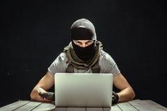 Terrorist working. On his computer stock image