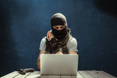 Terrorist working. On his computer royalty free stock image