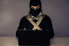 Terrorist working on his computer. Royalty Free Stock Image