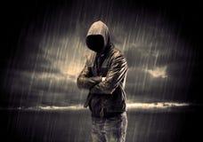 Terrorista anónimo en sudadera con capucha en la noche imagenes de archivo