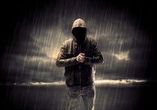 Terrorista anónimo en sudadera con capucha en la noche fotos de archivo