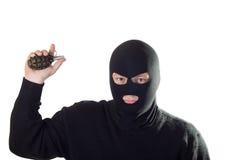 Terrorista en máscara con la granada. Foto de archivo