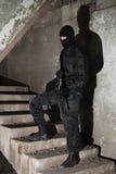 Terrorista en máscara negra en escalera fotografía de archivo libre de regalías