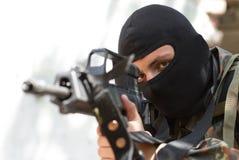 Terrorista na máscara preta com um injetor foto de stock royalty free
