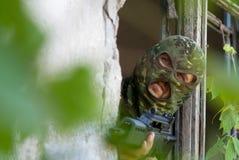 Terroriste armé regardant hors de l'hublot images stock