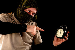 Terroriste avec une horloge photos stock