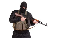 Terroriste dans l'uniforme noir et masque avec la kalachnikov d'isolement photos stock