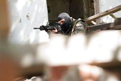 Terroriste dans le masque noir avec un canon photo libre de droits