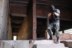 Terroriste dans le masque noir visant avec un canon photo libre de droits