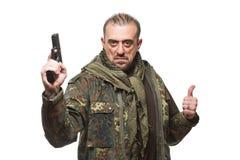 Terroriste masculin dans une veste militaire avec une arme à feu dedans photographie stock