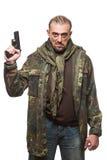 Terroriste masculin dans une veste militaire avec une arme à feu dedans images stock