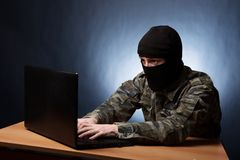 Terroriste travaillant sur son ordinateur Terroriste masqué de cyber entaillant l'intelligence d'armée photo stock