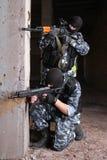 Terrorister i svarta maskeringar med trycksprutor Arkivbilder