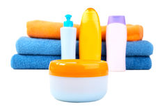 Terry towels and tubes with cosmetics isolated Stock Image