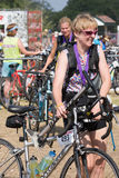 Terug het lopen van haar auto na een triatlon die een vloerpomp dragen Stock Foto's