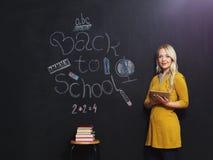 Terug naar de leraar van de schoolvrouw het glimlachen door bord Stock Fotografie