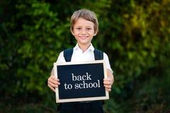 Terug naar het Concept van de School Van de de jongensholding van de basisschoolstudent het bordachtergrond Leuke Kaukasische pri royalty-vrije stock fotografie