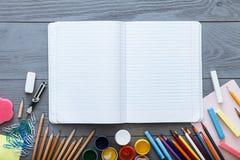 Terug naar het concept van de schoolverkoop, open leeg voorbeeldenboek op grijs donker bureau met kleurrijke potloden, verven, an stock afbeelding