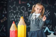 Terug naar school! Een klein blondemeisje in school eenvormige tribunes met twee zeer grote potloden op floore tegen bord met royalty-vrije stock foto