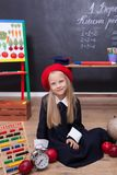 Terug naar school! Een meisje in school eenvormige zitting in een les Antwoordt aan de les Op het bord in de Oekraïense taal stock afbeeldingen