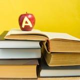 Terug naar school en kennisconcept Stapel van boeken en verse rode appel met teken A op houten achtergrond en in gele muur stock foto's