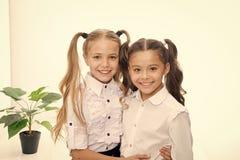 Terug naar School Gelukkige meisjes in eenvormig Terug naar het Concept van de School Meisjes met modieus die haar op wit worden  royalty-vrije stock foto