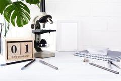 Terug naar School Groep schoollevering, microscoop en houten kalender met datum 1st September Stock Foto's