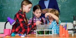 Terug naar School jonge geitjes in laboratoriumlaag het leren chemie in schoollaboratorium Chemielaboratorium het maken van exper stock foto's