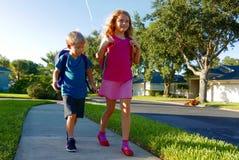 Terug naar school: Jongen en meisje die met rugzakken lopen royalty-vrije stock fotografie