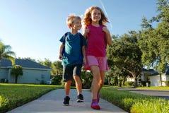 Terug naar school: Jongen en meisje die met rugzakken lopen royalty-vrije stock foto's
