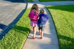 Terug naar school: Jongen en meisje die met rugzakken lopen royalty-vrije stock afbeeldingen