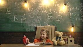 Terug naar School Leerling die bij het bureau bestuderen Kind in de klassenruimte met bord op achtergrond Klok, potloden, boeken stock videobeelden