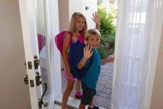 Terug naar school: Meisje en jongen die de voordeur opstappen stock foto's
