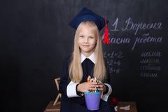 Terug naar school! Vrolijk meisje op school op een zwarte achtergrond Het onderzoeken van de camera Het concept van de school Sch stock foto