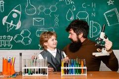Terug naar school, wetenschap en onderwijs voor leerlingskind Leraar die jonge jongen met les helpen Het vrolijke weinig glimlach royalty-vrije stock foto's