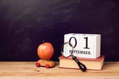 Terug naar schoolachtergrond met boek, stuk speelgoed auto, appel en kalender Stock Fotografie