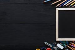Terug naar schoolachtergrond met kantoorbehoeftenlevering voor modern elementair onderwijs, kleurenpotloden, verven en kader op d royalty-vrije stock fotografie