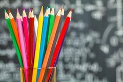 Terug naar schoolachtergrond met kleurrijke gevoelde pennen en vage die wiskundeformules door wit krijt op het zwarte schoolbord  stock afbeelding