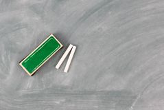 Terug naar schoolconcept met groen bord plus gom en krijt stock foto