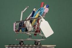 Terug naar schoolmalplaatje met veelvoudige kantoorbehoeften in het winkelen karretje Stock Afbeeldingen