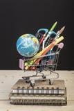 Terug naar schoolmalplaatje met veelvoudige kantoorbehoeften in karretje Stock Foto's